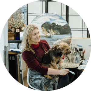 Photo of me in the studio with paintbrush in hand with my helpful companion Grace